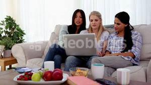 Friends pointing and looking at laptop