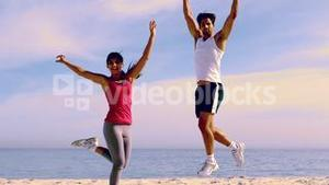 Couple jumping with hands up