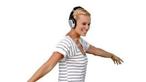 Young woman listening to music on white background