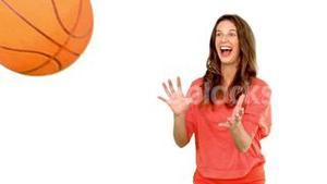 Smiling woman catching a basket ball on white background