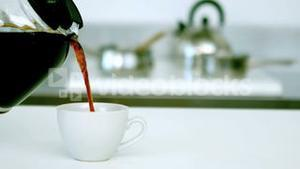 Coffee being poured into cup of coffee