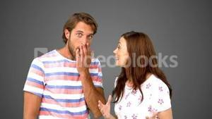 Woman telling her friend a massive secret on grey background