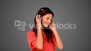 Woman listening to music on grey background
