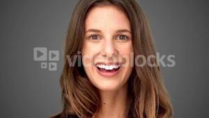 Surprised woman smiling on grey background