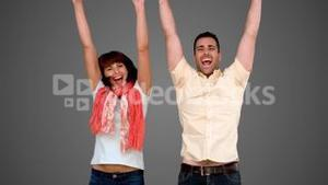 Two friends jumping on grey background