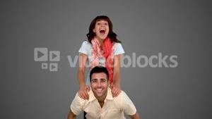 Woman jumping on the back of her friend on grey background