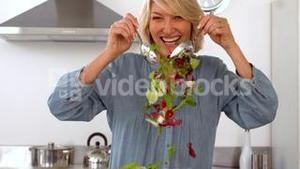 Smiling woman tossing her salad
