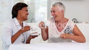 Two mature women gossiping during afternoon tea