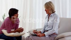 Woman sitting on sofa talking to therapist