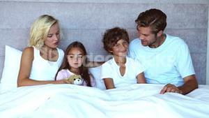 Family sitting in bed
