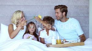 Family sitting in bed and having breakfast in bed