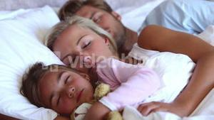 Parents and daughter sleeping peacefully