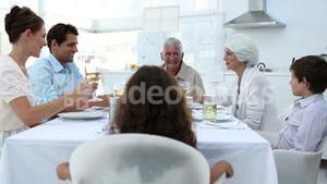 Family sitting at dinner table and toasting
