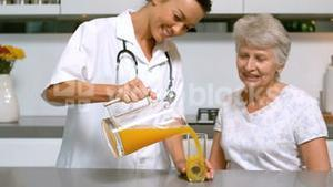 Home help pouring orange juice for patient in kitchen