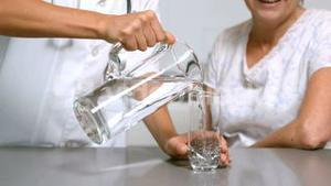 Home help pouring water for patient in kitchen
