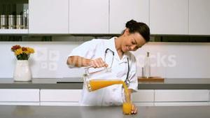 Home nurse pouring glass of orange juice in kitchen