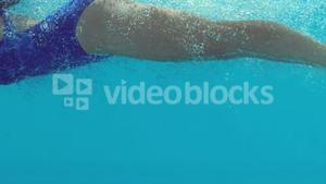 Woman in blue bathing suit swimming underwater