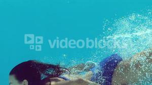 Woman in blue swimsuit swimming underwater