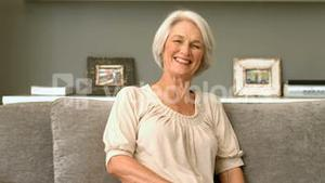 Happy retired woman smiling on couch