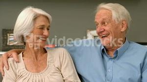 Elderly couple laughing in their home