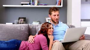 Couple using laptop on couch