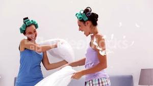 Friends in hair rollers having pillow fight