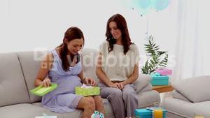 Expectant mother opening a present from friend