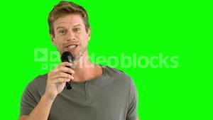 Man with microphone singing on green screen