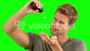 Man pouring out pills on green screen