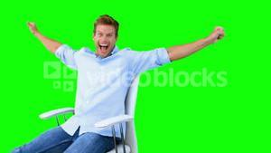 Man sitting on swivel chair with raised arms to show his success on green screen