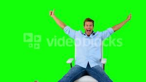 Man on swivel chair giving thumbs up on green screen