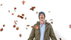 Amazed man looking at falling leaves on white screen