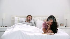 Woman reading a book while partner is sleeping
