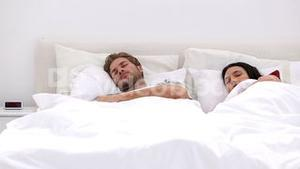 Couple sleeping peacfully with partner pressing snooze
