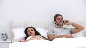 Man talking on phone while his partner is sleeping
