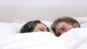 Couple cozied up under the covers