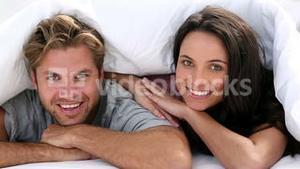 Attractive couple cozy under the covers