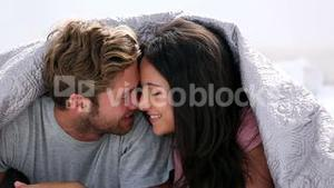 Couple being romantic under the covers