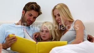 Parents and daughter reading book together