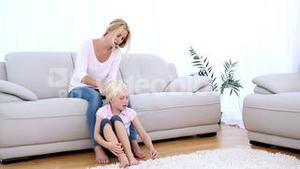 Mother playing with daughters blonde hair