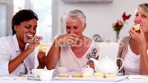 Retired women having cupcakes and tea together