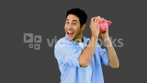 Man shaking piggy bank excitedly on grey background