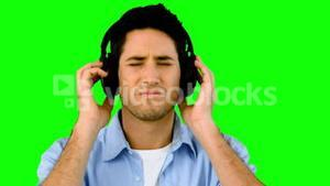 Man listening to music with headphones on green screen