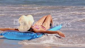 Girl sunbathing on a lilo on the beach getting splashed by the waves