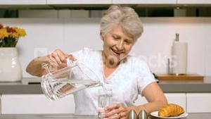 Elderly woman pouring a glass of water for breakfast