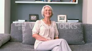 Retired woman laughing on the couch