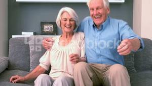 Retired couple sitting down on the couch and smiling