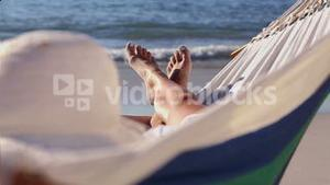 Woman relaxing on the beach in a hammock