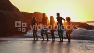 Silhouettes of friends having fun on the beach
