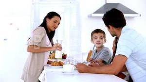 Mother pouring milk at family breakfast